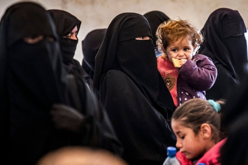 Women and children stand in Al-Hol camp