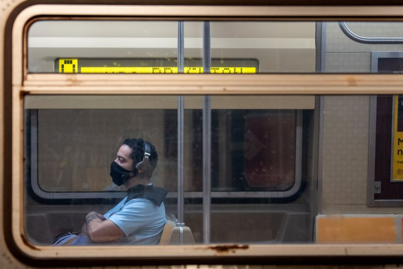 A man wearing a facemask on train