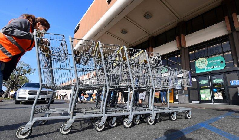 Food 4 Less worker pushing carts