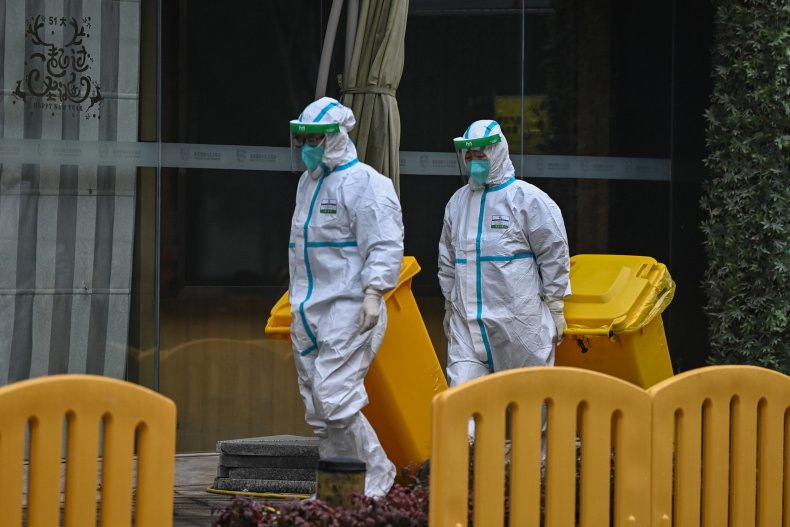 Workers wearing protective gear are seen in
