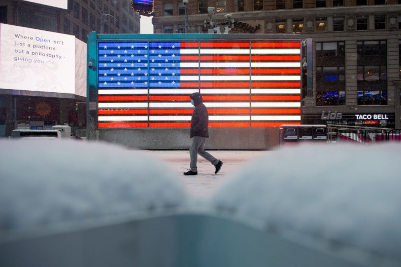 Person in facemask walks past American flag