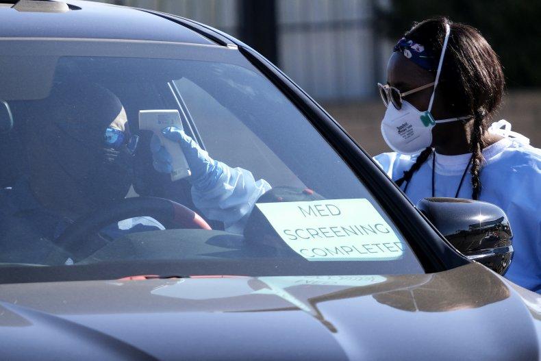 Health worker checks temperature of motorist