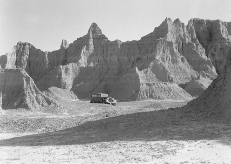 Vehicle and Badlands geological formations