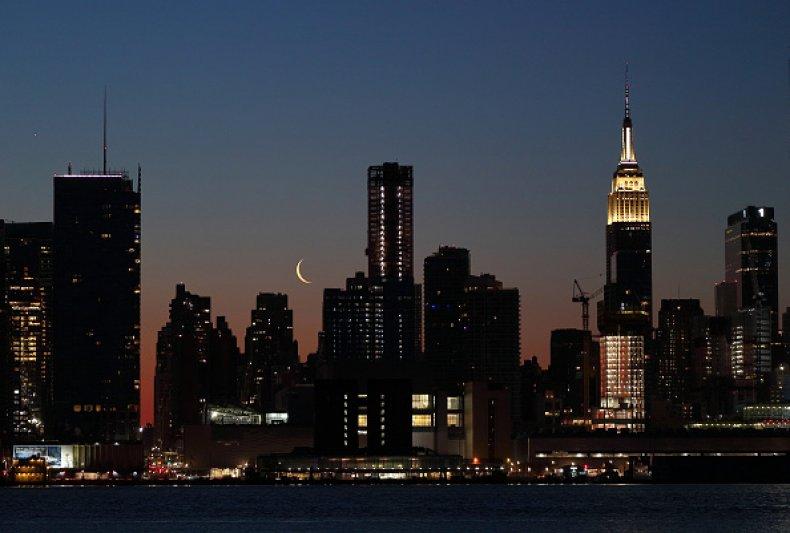 A crescent moon rises behind the Empire