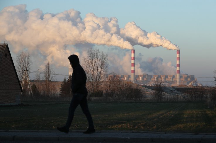 Man walks past coal plant