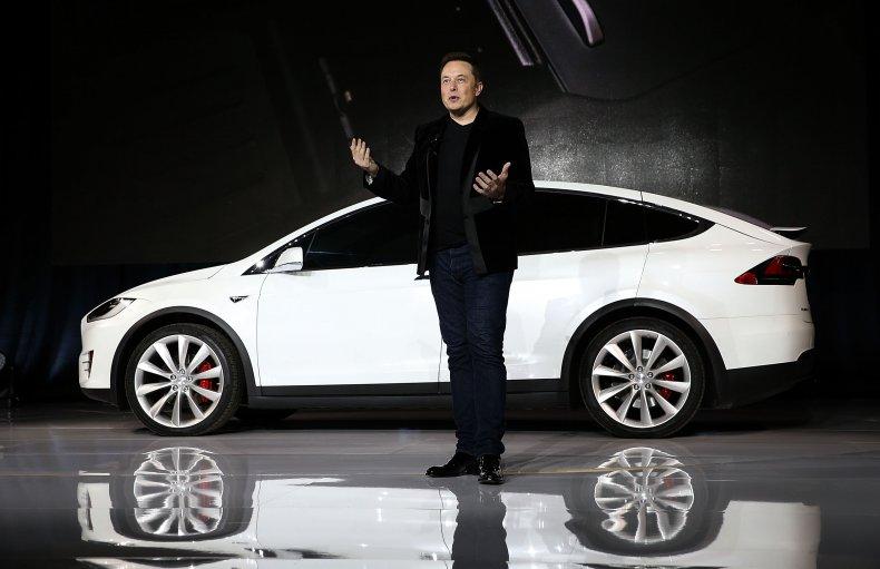 Elon Musk standing by a Tesla