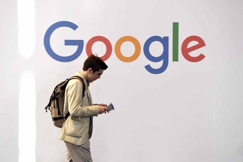 Man walks past google logo