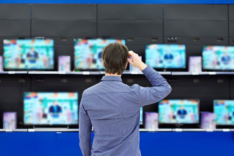 Man looks at televisions