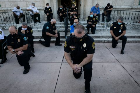 police officers take a knee