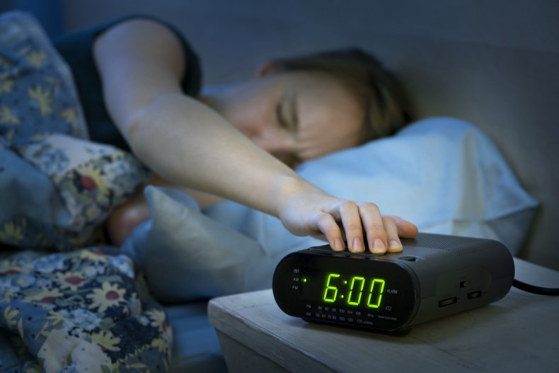 Woman pressing a snooze button