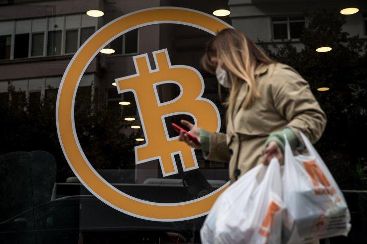 Woman walks past Bitcoin sign