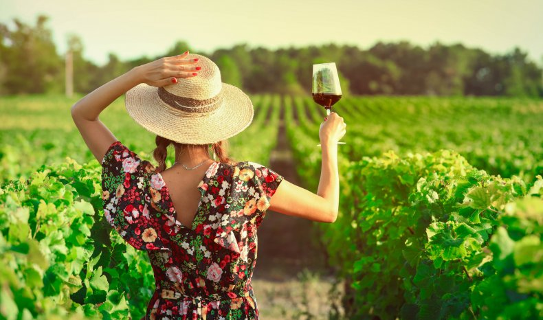 Woman drinking red wine at vineyard