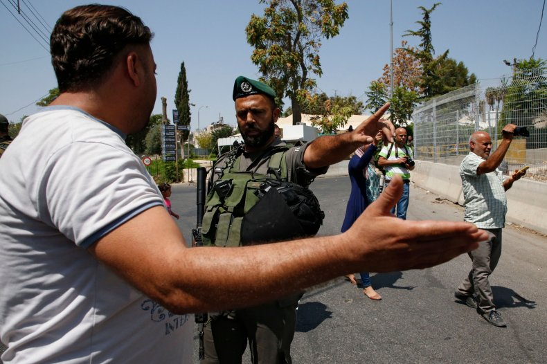 An Israeli policeman argues with a Palestinian
