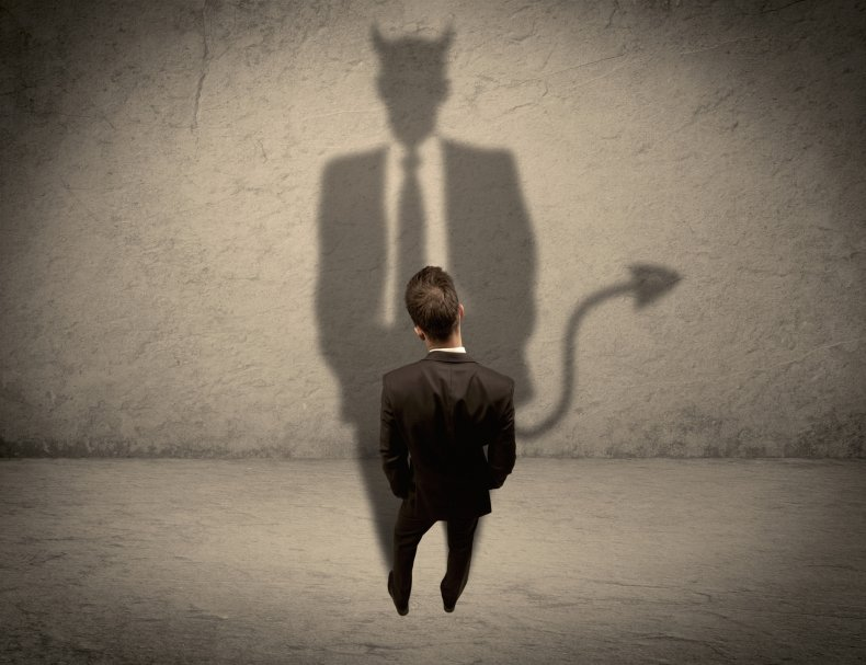 Man in suit looking at his shadow