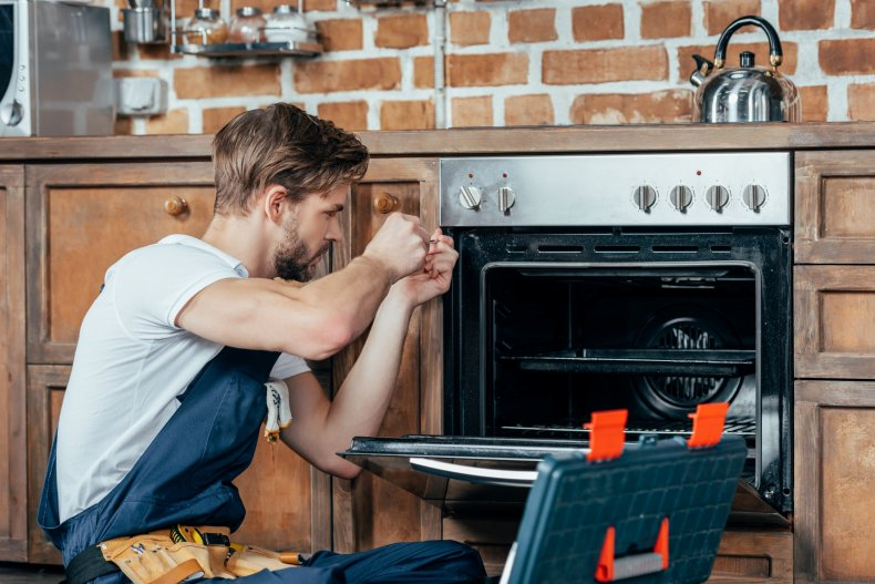 Stock image of man fixing an oven
