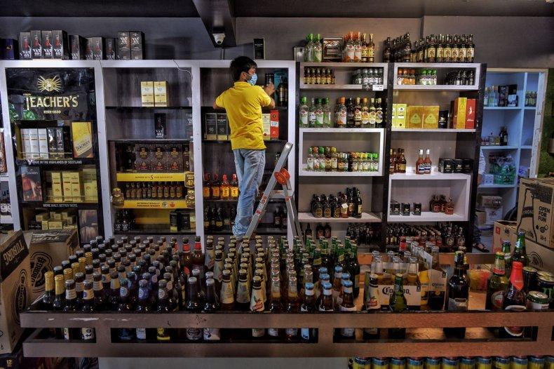 A man stocks liquor store shelves.