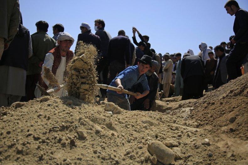 Afghan Men Bury Bombing Victim