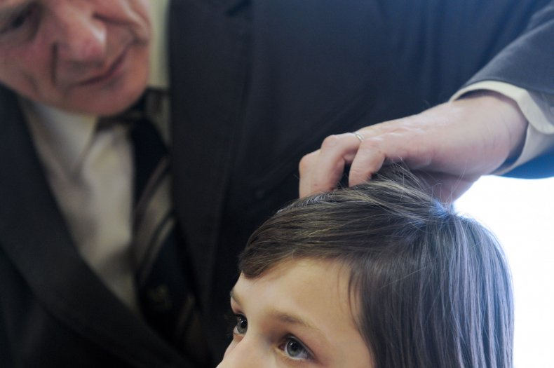 A man inspects hair for head lice.