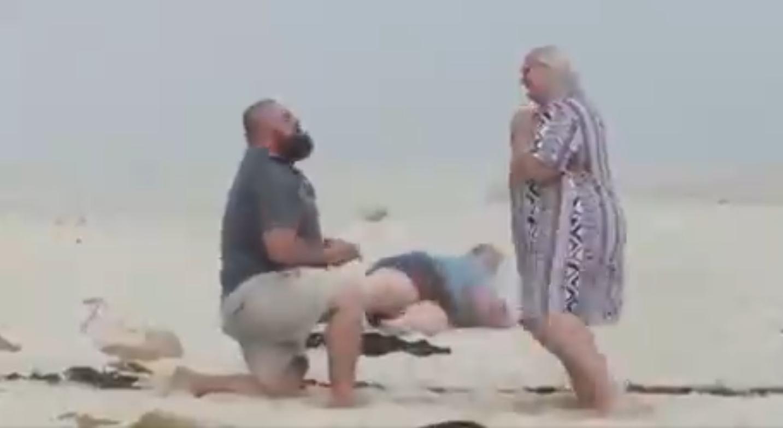 man proposing beach photographer falls.