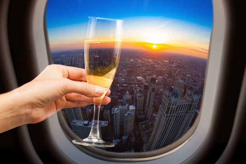 Woman holding wine on a plane