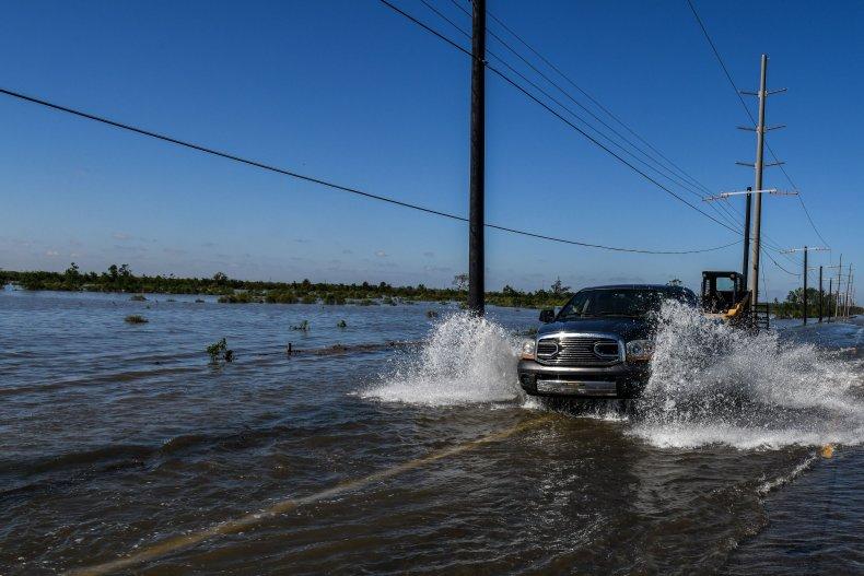 Car drives through flooded Louisiana street