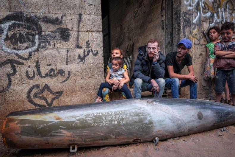 Palestinians sit by Israeli bomb in Gaza