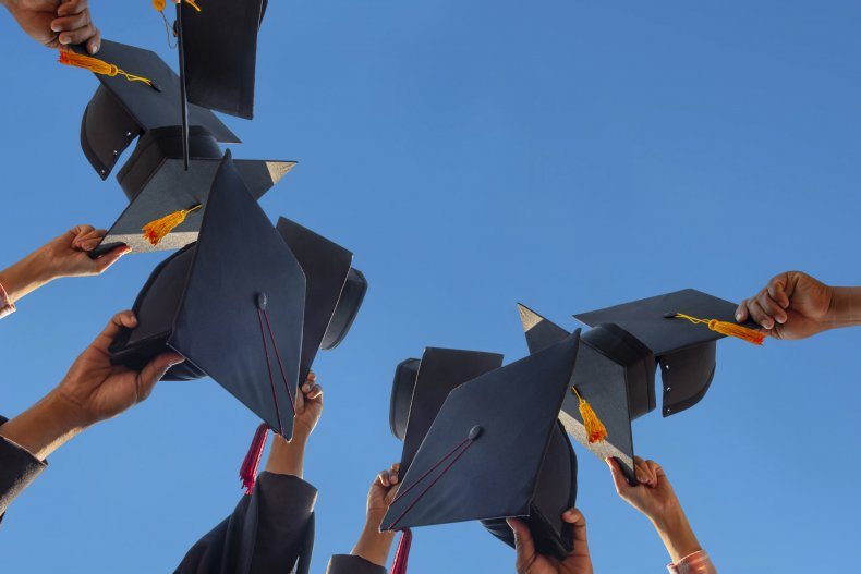 Graduating students holding mortarboard hats