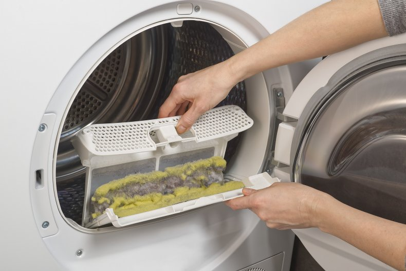 Woman cleaning the trap of a dryer.