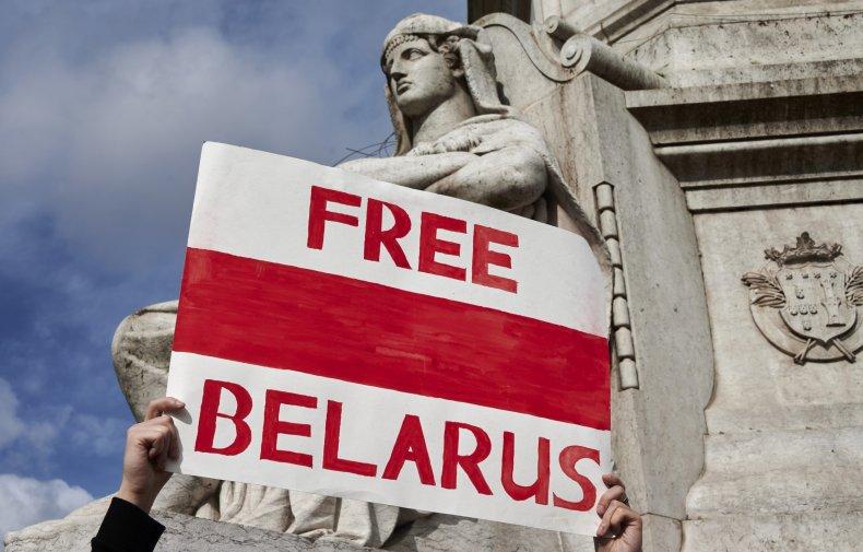 A demonstrator hoists a Free Belarus poster