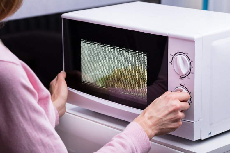 Woman Using Microwave Oven For Heating Food
