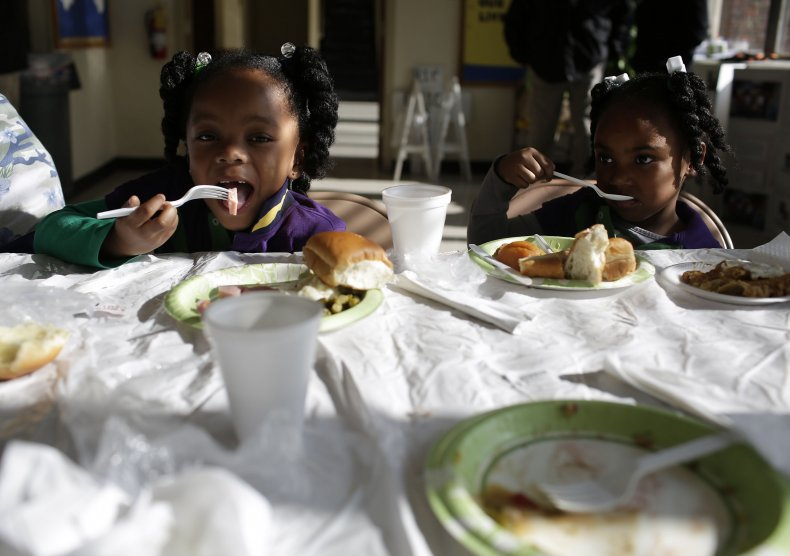 Two little Black girls eat a meal.