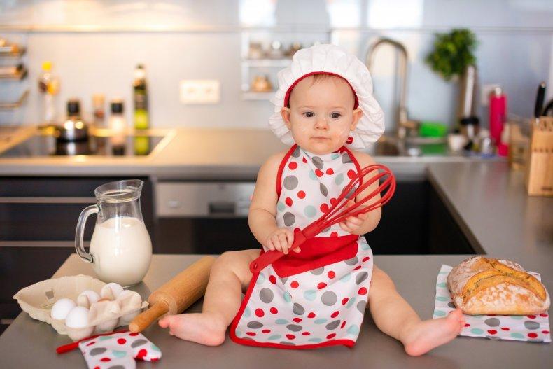 baby holding whisk kitchen
