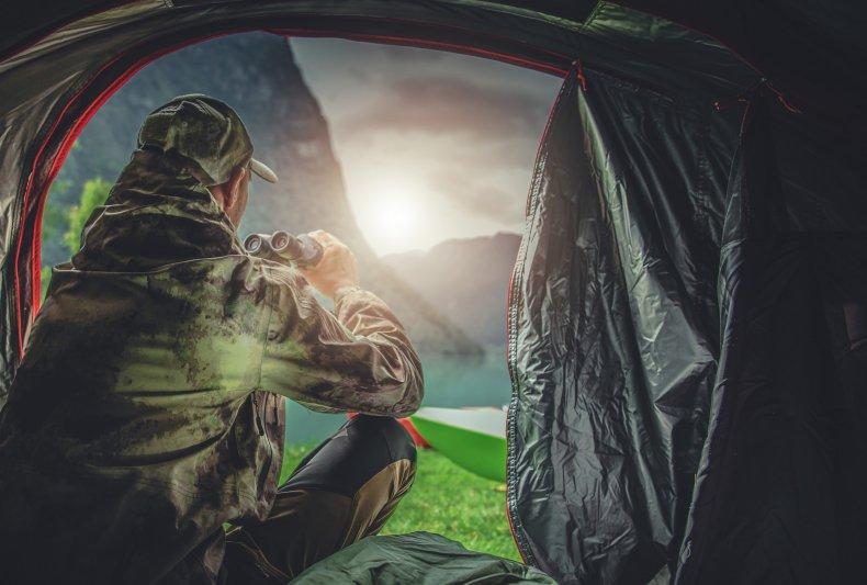 A hunter in his tent using binoculars