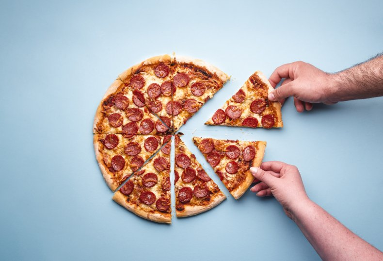 Two people taking pepperoni pizza slices
