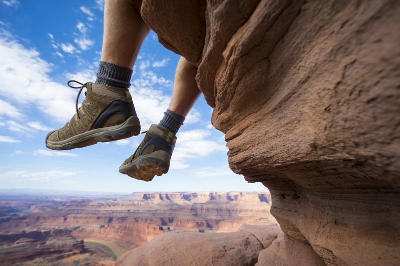 Hiker Resting with Boots Dancing Above Canyon