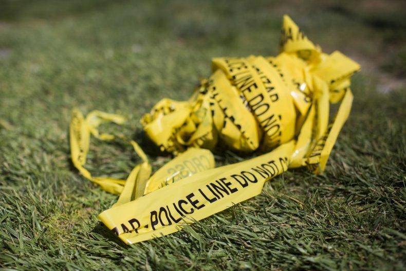 Crime scene tape lies on grass.