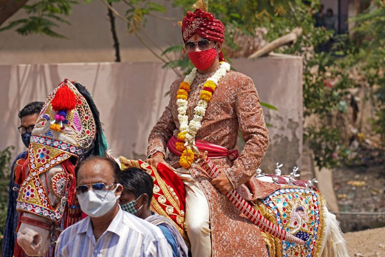 An Indian groom rides a horse.