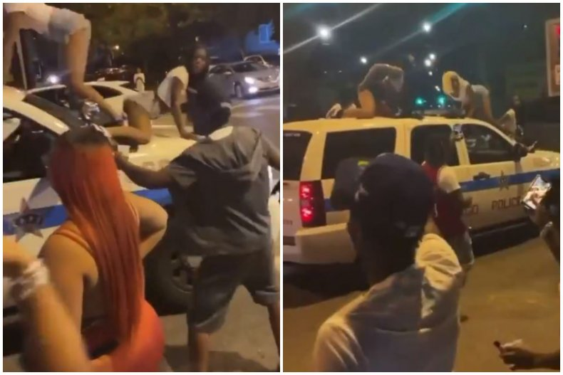 People dance on a Chicago Police SUV