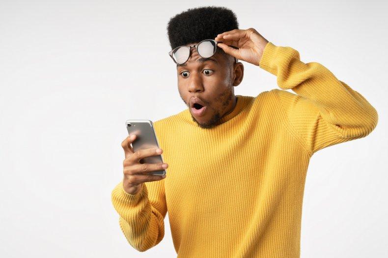 Man looking at phone in shock