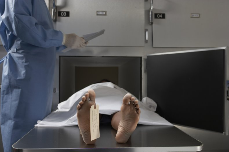A mortician looking over a body