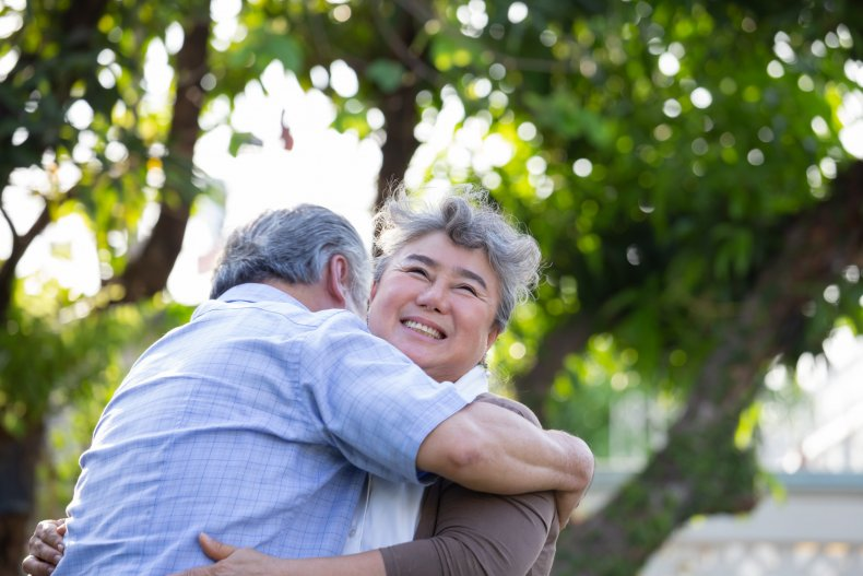 Two elderly people embracing