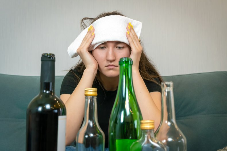 Hungover woman looking at bottles.