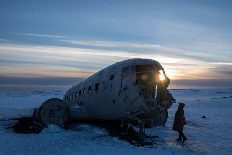 Tourist viewing plane wreck in Iceland.