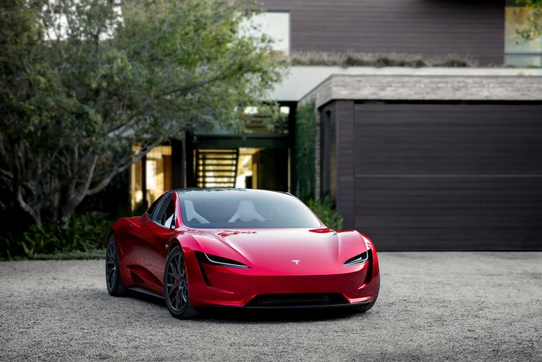 Tesla Roadster parked red house driveway