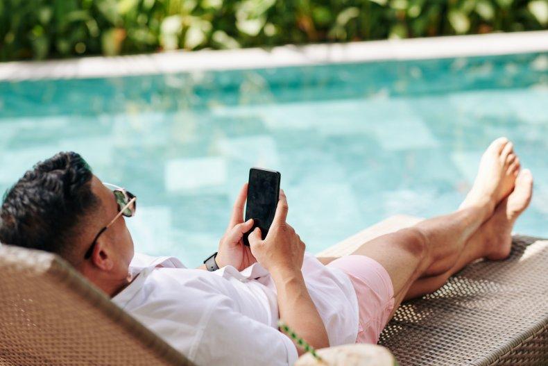 man sitting on phone by pool