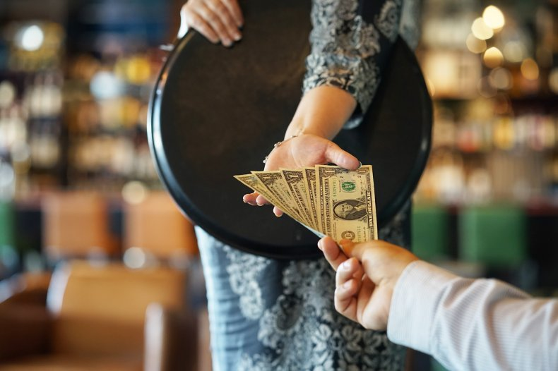Customer tipping cash to waitress