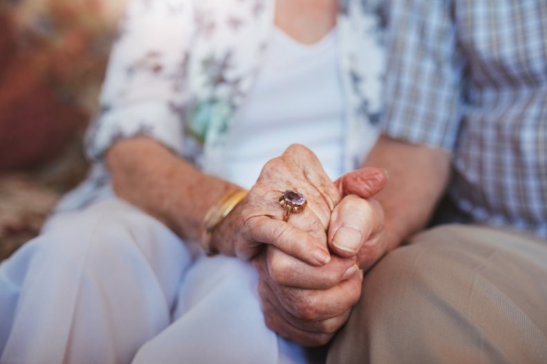 elderly man and woman holding hands