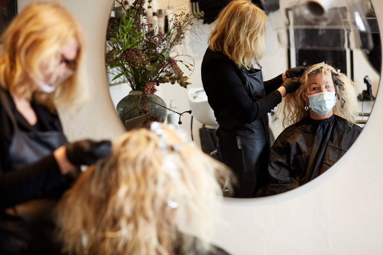 A Danish hairstylist dyes a client's hair.