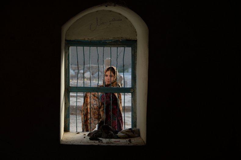 An Afghan girl looks through a window