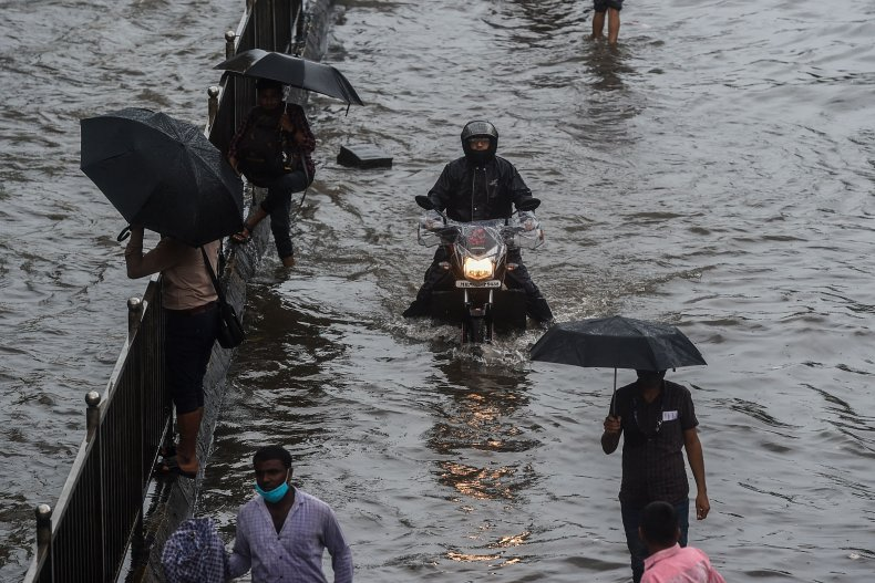 Commuters make their way through flooded roads